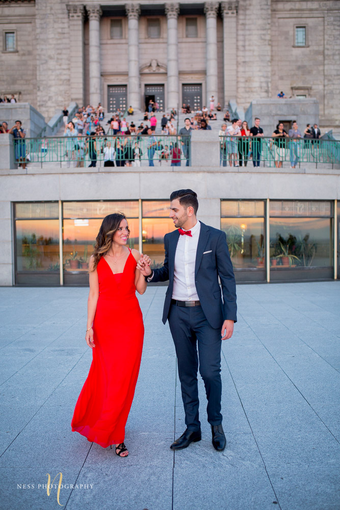 couple holding hands in front of saint joseph oratory during montreal engagement session with crowd watching behind