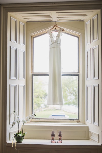 minimalist bridal dress hanging in window- Forest and Steam Club Wedding by Ness Photography Montreal wedding photographer- Bride getting ready-.jpg