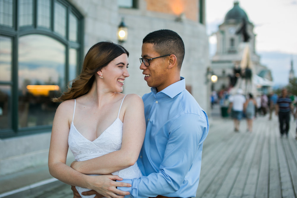 couple hugging and smiling in front of chateau frontenac