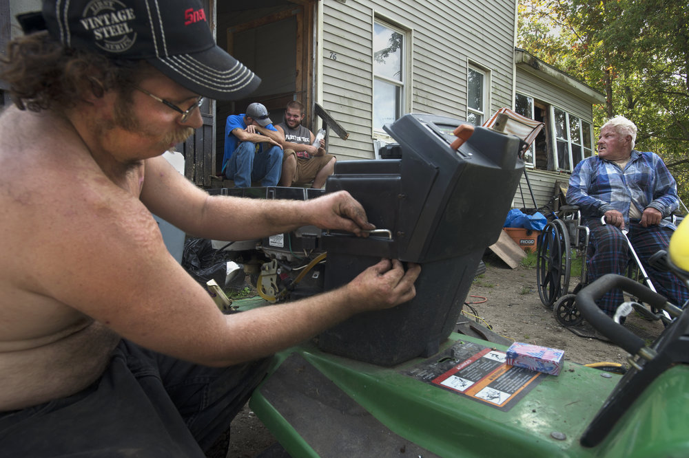 Gregory Aldrich, 27, from left, Aaron Bush, 28, Kevin Aldrich, 28, and John Bush, 85, relax in their front lawn as Gregory rewires his lawnmower on Monday, Sept. 18 2017 in Gouverneur.(Christian K. Lee/Watertown Daily Times)