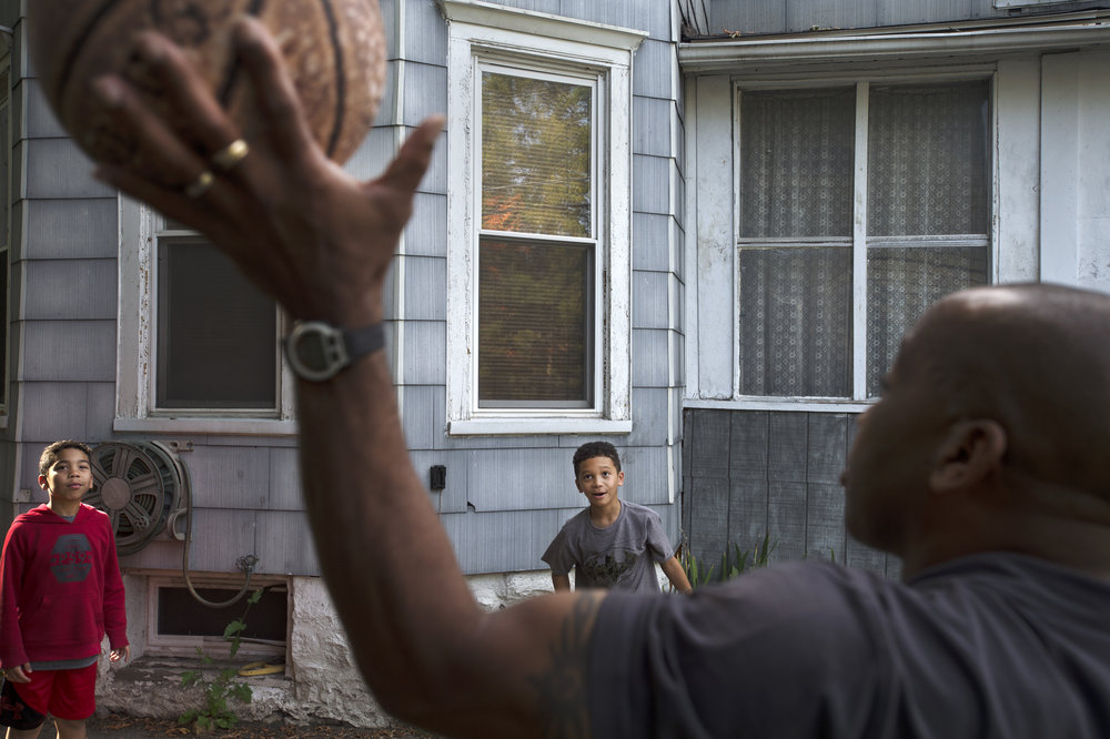 Isaiah Matthews, 11, from left, and his brother Benjamin Matthews, 8, play basketball with their father Anthony Matthews, 53, outside of their on Tuesday, Sept. 19 2017 in Watertown. Anthony waits for his sons' to get home from school daily to spend time with them.(Christian K. Lee/Watertown Daily Times)