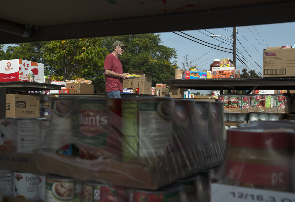 Bob Witham, 69, carries a box of cans during a food collection drive at St. Anthony's Church on Friday, Sept. 15 2017 in Watertown. Withal is volunteering at the drive.(Christian K. Lee/Watertown Daily Times)