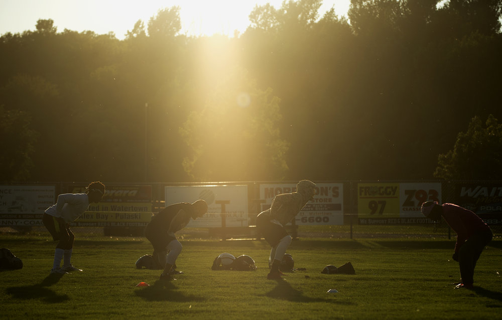 Sunlight illuminates Red and Black semi-pro football players during their practice at the Alex T Duffy Fairgrounds on Tuesday, Sept. 12 2017 in Watertown, New York.(Christian K. Lee/Watertown Daily Times)