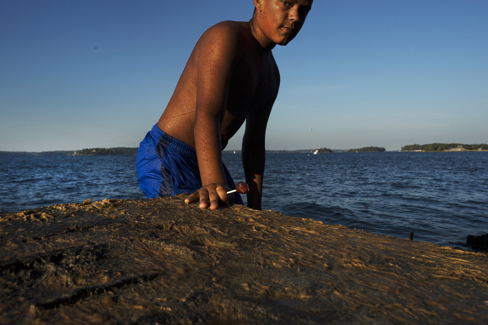 Jacob Mitchell, 12, exits the St. Lawrence River with his lollipop in hand after jumping into during a Jazz Festival on Saturday, Sept. 23 2017 in Clayton.(Christian K. Lee/Watertown Daily Times)