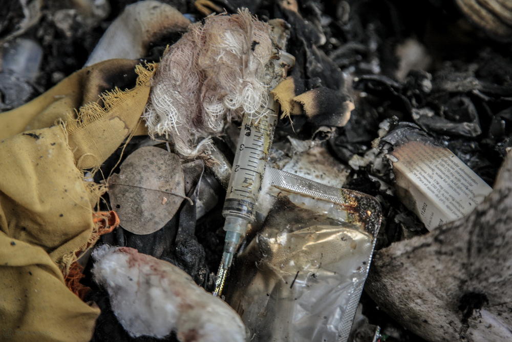 One of thousands of used needles poking out of the waste pile