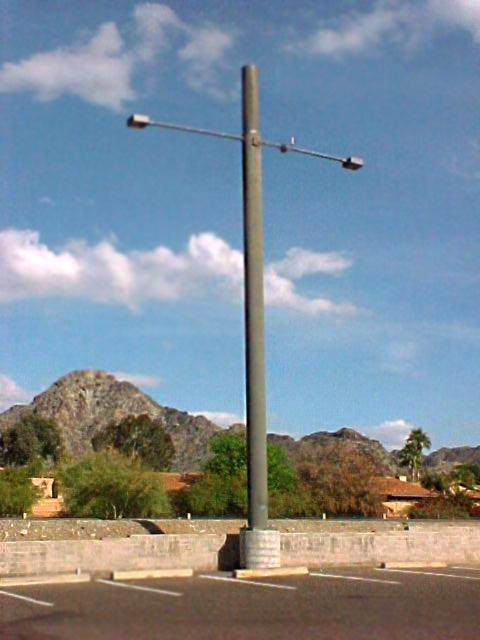 New light pole installations in a commercial parking lot.