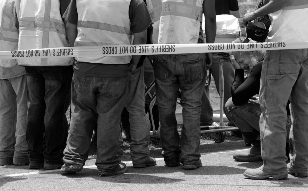 Construction workers gather to pray around the body of one of their coworkers after local fire departments extracated his body from a construction accident on Scuffletown Road in Fountain Inn.  (June 14, 2012)