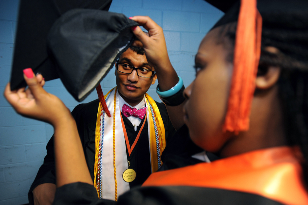 Tamera Fowler, right, helps Mohit Gandhi, left, with his cap before the start of Southside High's graduation ceremony.