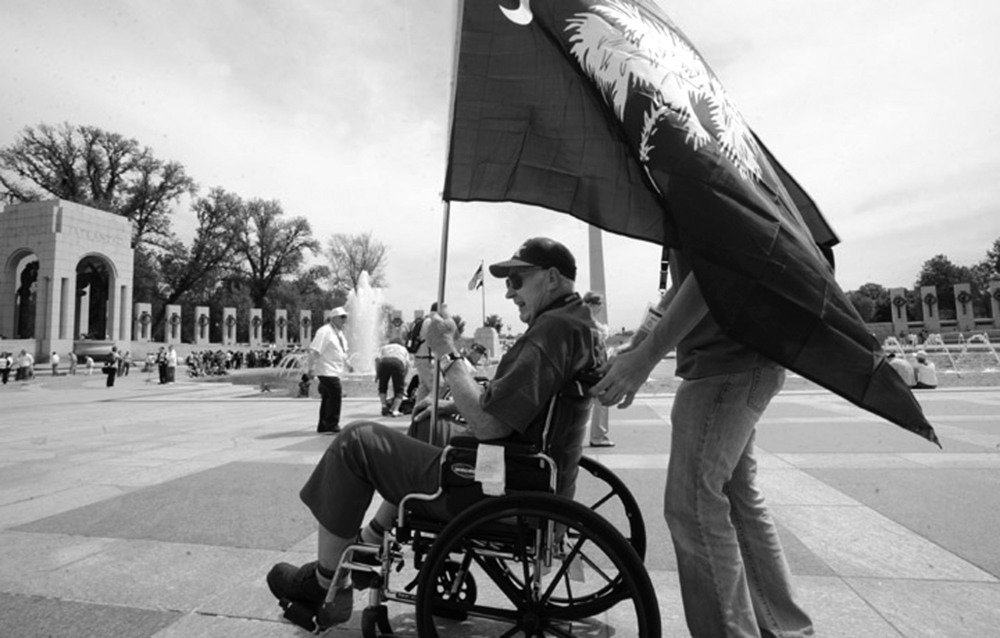 A veteran carries a South Carolina state flag through the World War II Memorial in Washington, D.C. He was part of a group of South Carolina World War II veterans to travel to Washington as part of Honor Flight Upstate.