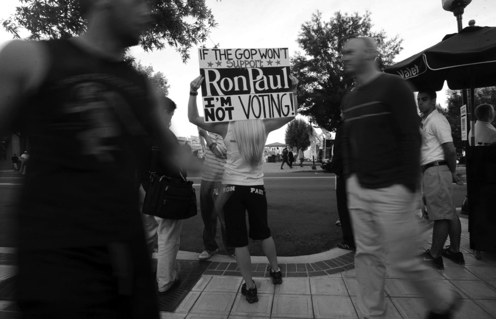 A Ron Paul supporter waves a sign for people walking along Main Street in Greenville, S.C., before the start of the South Carolina republican presidential debate.