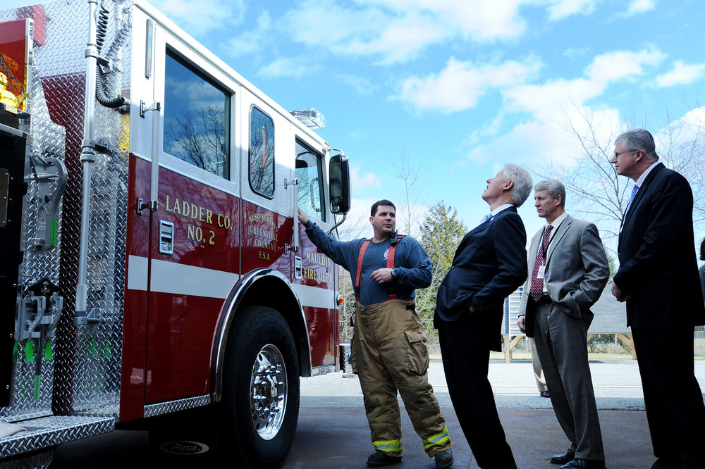 President Bill Clinton, center, looks up at a Mauldin Fire Department truck while being given a tour of the firefighting program at the Golden Strip Career Center in Mauldin, S.C., by instructor Jim Deese, left.