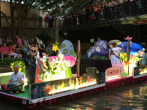 River barges with colorful adornments float along the Riverwalk. (Photo courtesy:   TexasCavaliersRiverParade/Facebook  )