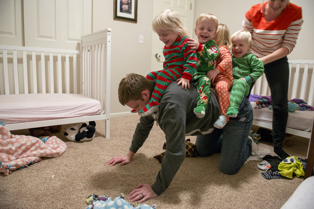 Cameron and Courtney play piggy back with their two-year old, quadruplets before bedtime on Nov. 21, 2014. Cameron loves to spend time with the kids once he is home from work since he doesn't get to see them all day.