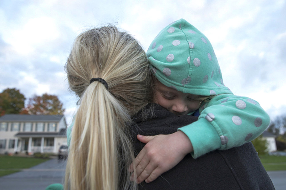 Courtney holds Kylie in an embrace as they wait for the bus on Oct. 24, 2016 in Lima, New York. The kids have been going to school at Kid Start since they were 2.5 because they were behind in speech in development.
