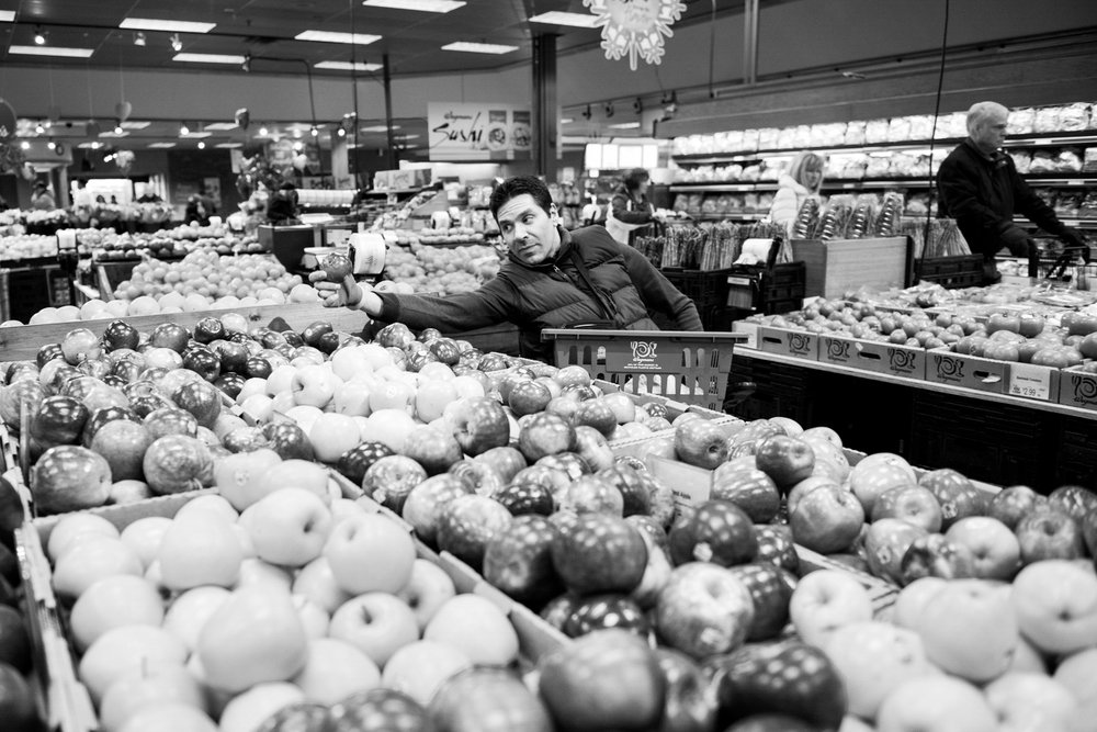 David struggles to reach the apple he wants at the local Wegmans. David often struggles to get things because of his disability, but has found alternative devices to help him