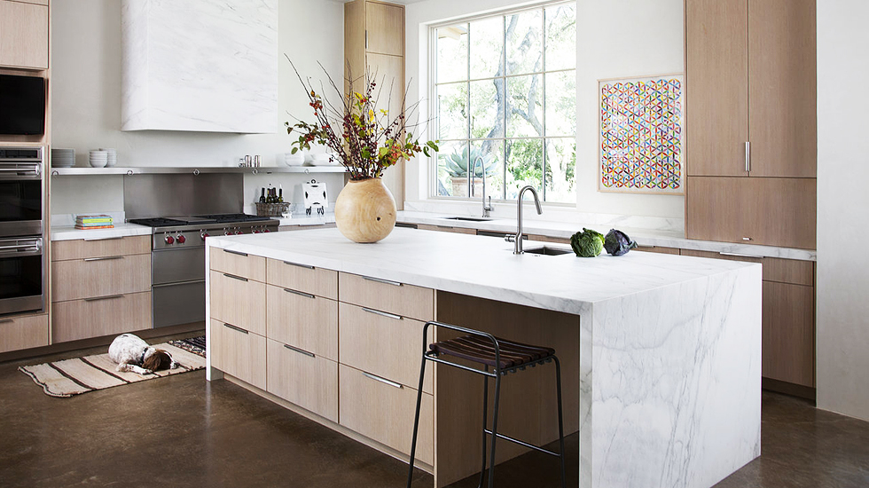 The waterfall island is design element we both really enjoy and love to see in the right space. We've never seen a range hood done in this material. That's what's so fun about design - there's always something innovative!{Via  Domaine Home }