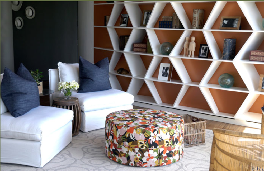 The lines of the bookshelf could almost be tribal inspired and the orange is so pretty, especially when contrasted with the navy and natural wood tones.  And the ottoman is just too much fun.