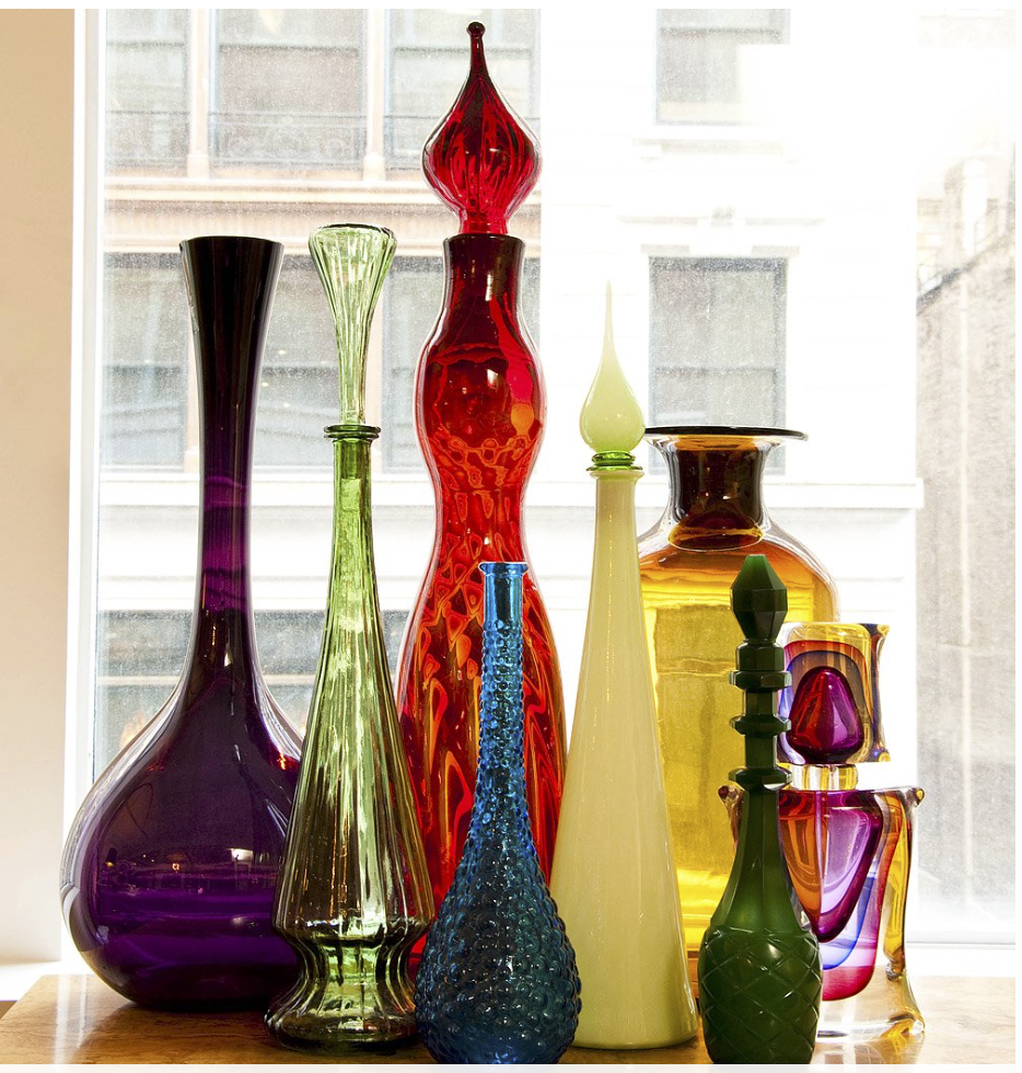 A collection of beautiful colored bottles, including some  Blenko  glass. {Via  Vogue }