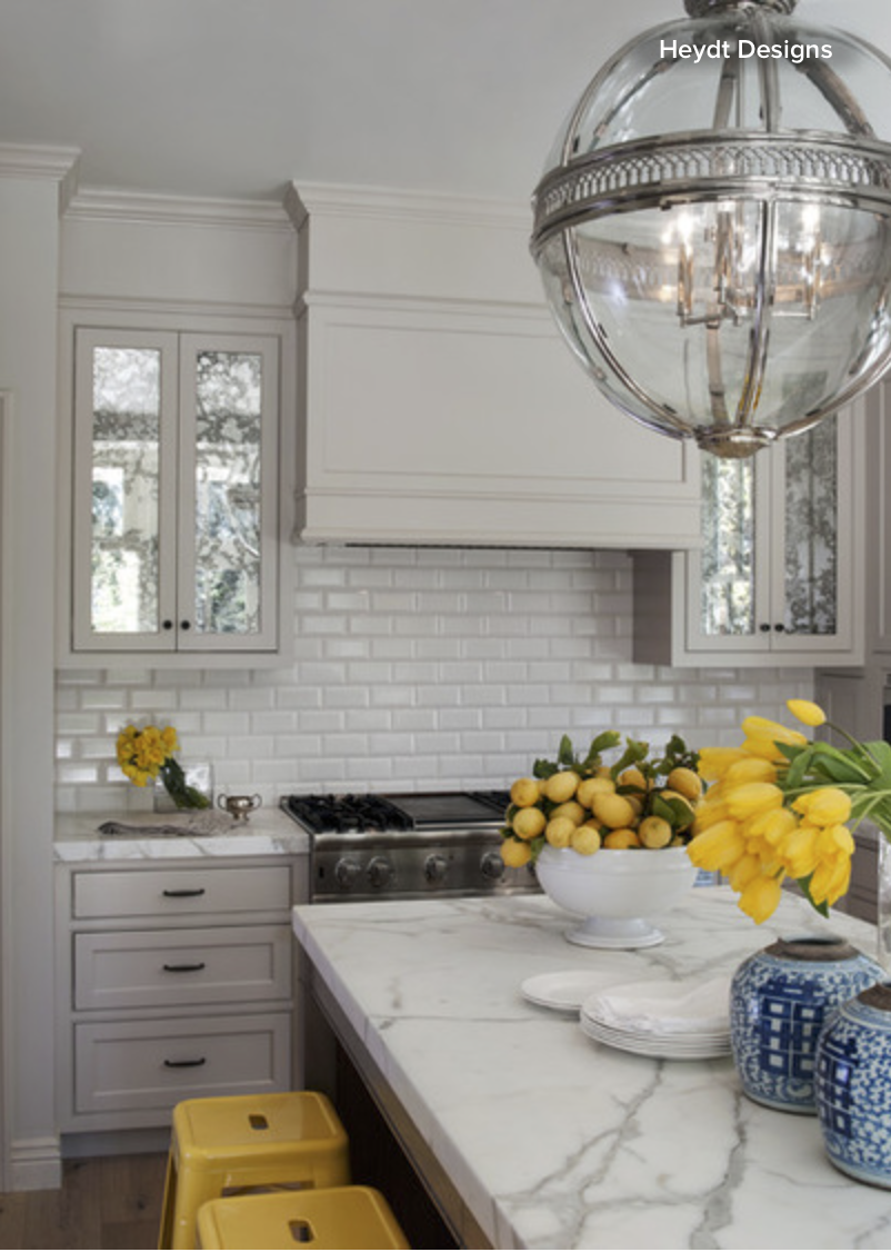 Try replacing your glass front cabinets with mirrors.  They'll keep the space feeling open and light, but you won't have to have a perfect vignette behind the closed doors.{Via Houzz}