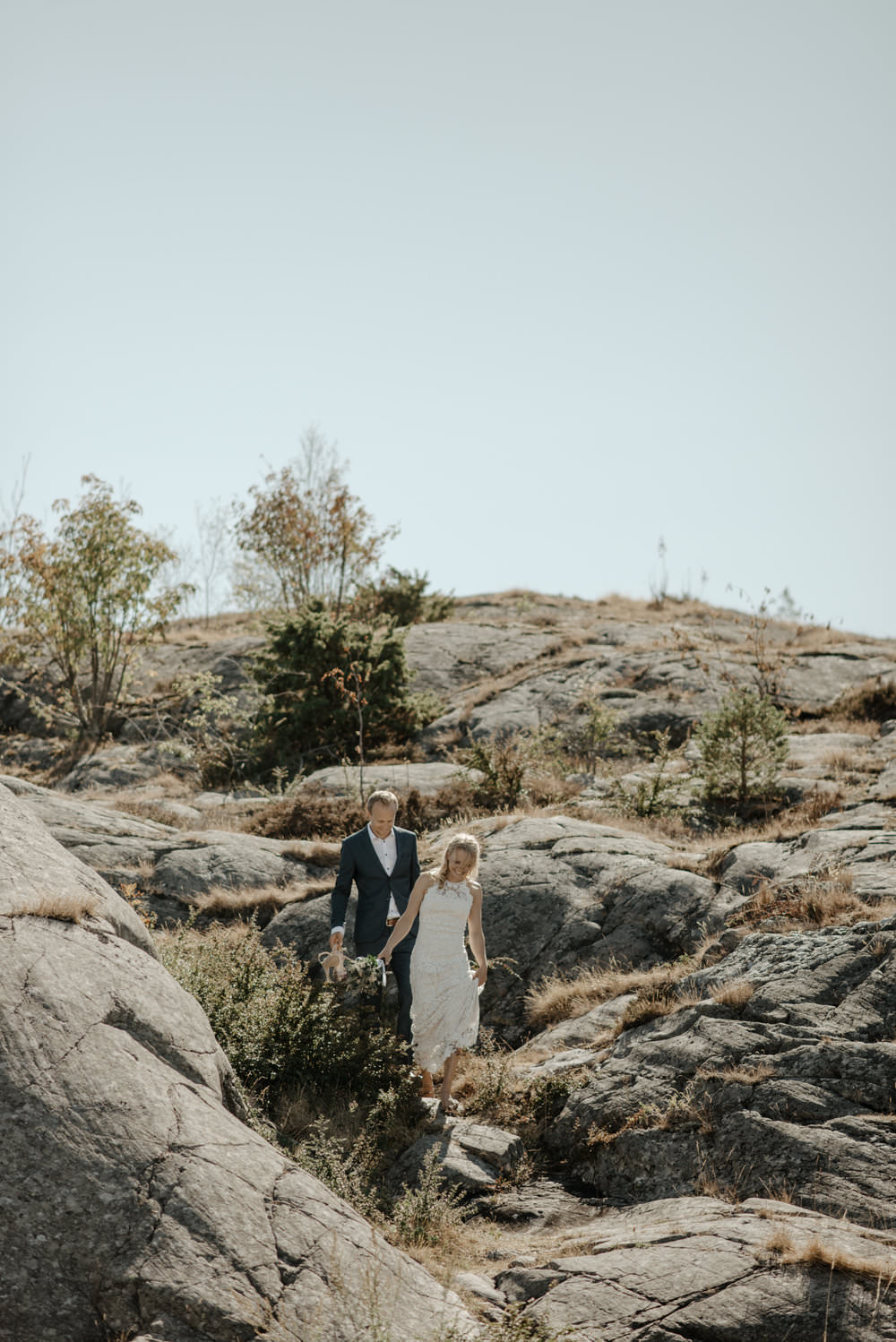 Couple climbing down to their cliffside wedding ceremony