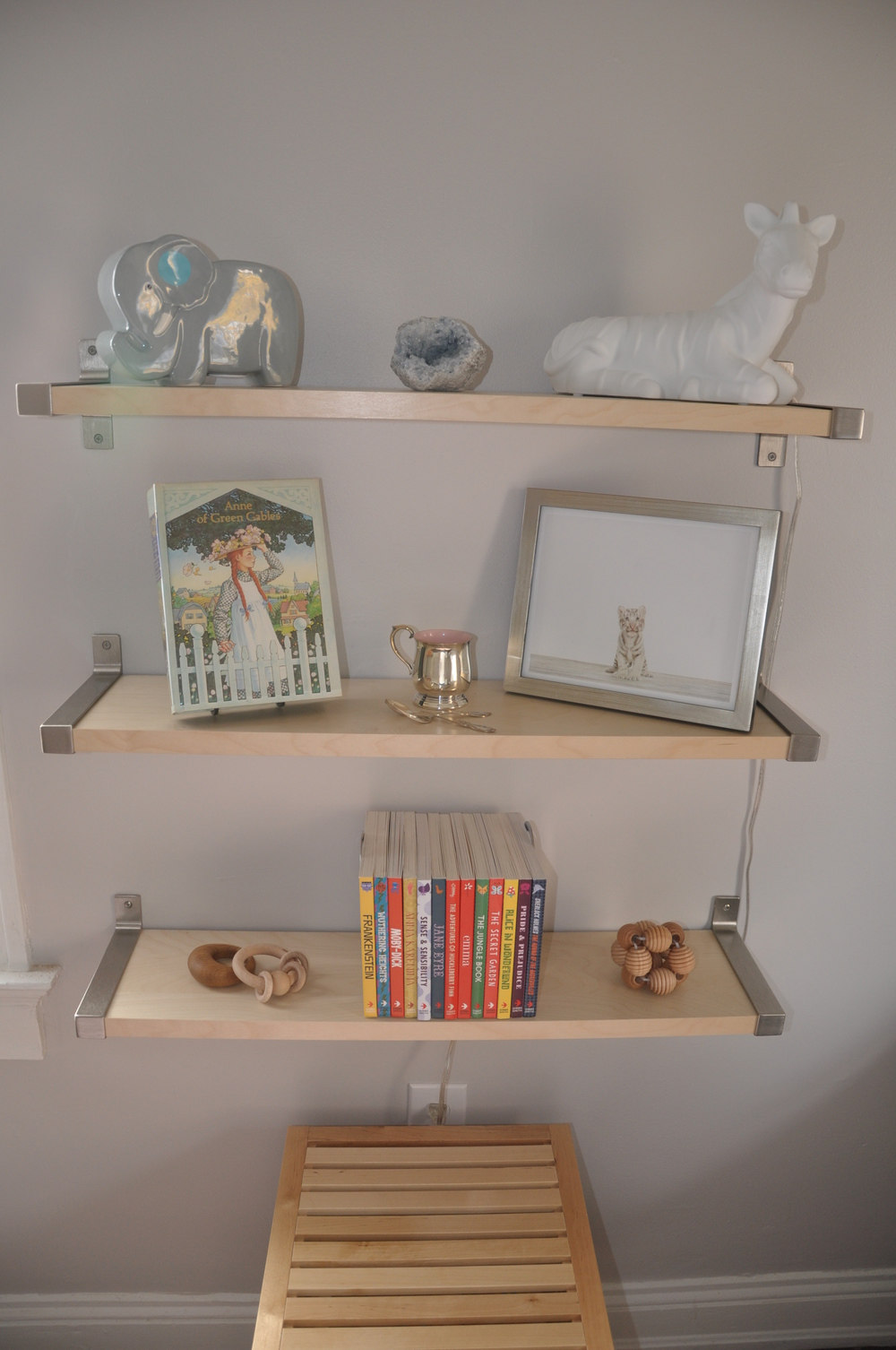 Top shelf: a blue celestine is good for sleep and connection to angelic realms. Middle shelf: my old copy of Anne of Green Gables. Bottom shelf: my friends know my preference & love of all wooden toys, and gifted accordingly.