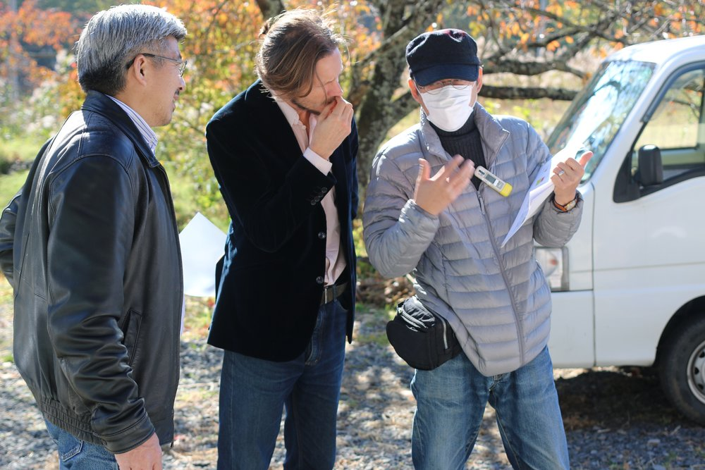 A team led by Prof. Koji Itonaga (right, wearing face mask and radiation monitor) is looking for ways to revitalise the collapsed agricultural sector around Fukuhima by switching to biofuel crops grown in contaminated soil. Photo:  Camilla S. Rose .