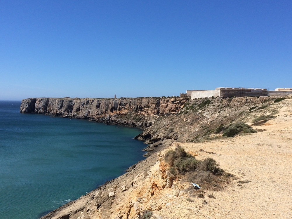 View of the Ponta de Sagres peninsula from Praia do Mareta  where you can see the fortress and the lighthouse.