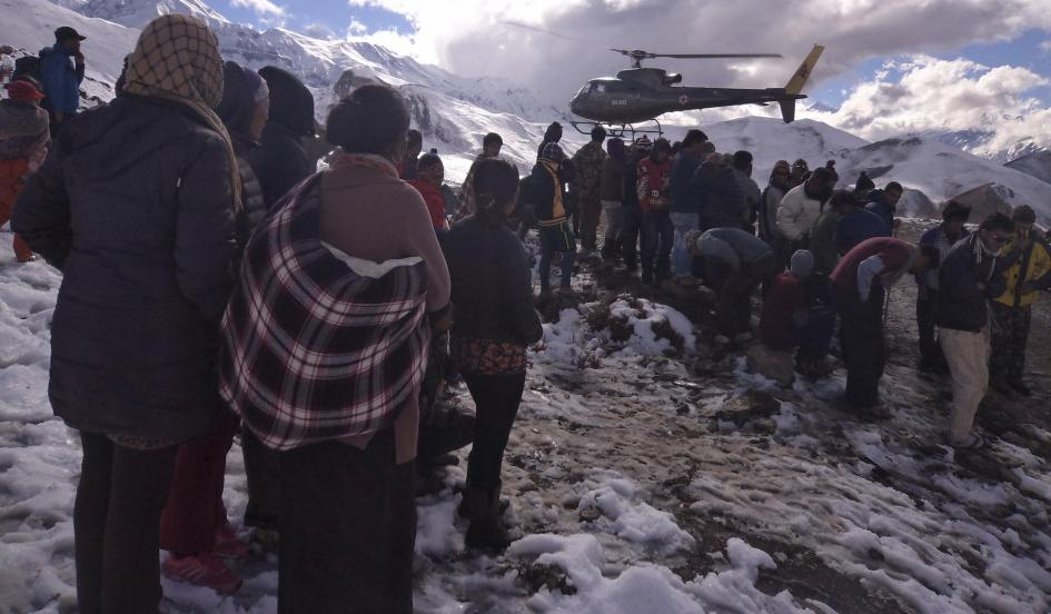 People gather near a helicopter belonging to Nepal Army used to rescue avalanche victims at Thorang-La in Annapurna Region in this October 15, 2014. Handout photo provided by Nepal Army.     Nepal Army/Reuters