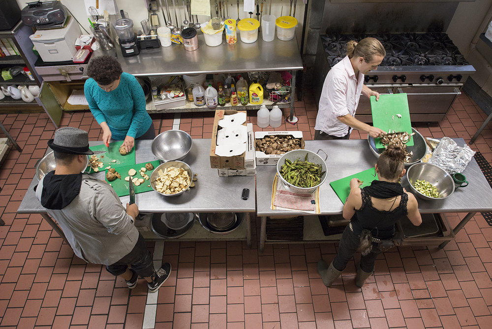 Volunteers from Food Not Bombs prepare recycled food for community dinner in the South Wedge neighborhood in Rochester, N.Y. on June 27, 2015.