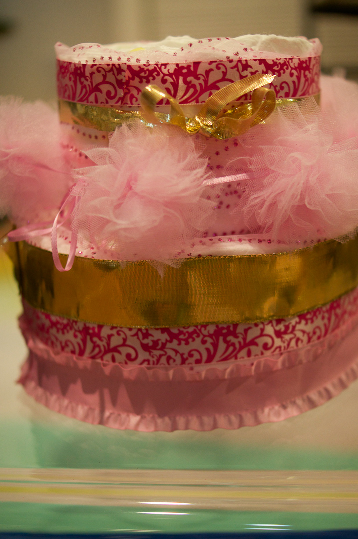 I chose to put just one ribbon on the top layer and tied a golden ribbon around it as a bow. The pink fluffy balls decorate the top of the base layer.