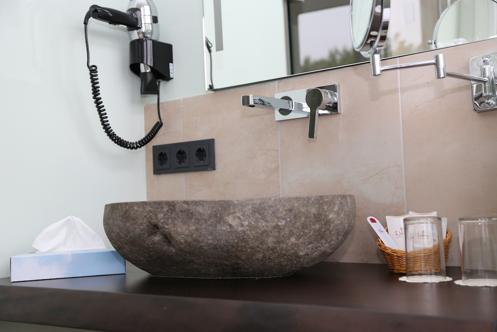 Badezimmer mit Waschbecken aus Flusssteinen