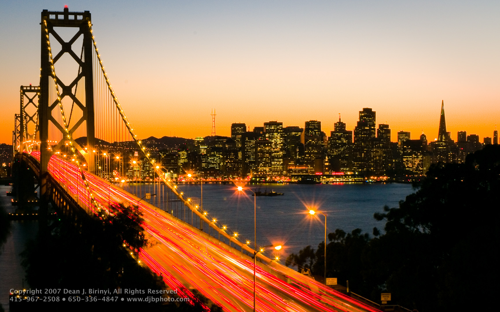 San Francisco Bay Bridge at sunset with illuminated cityscape in background