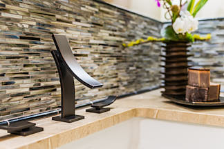 Contemporary faucet, backsplash and flowers in bathroom detail by San Francisco interior photogrpaher Dean Birinyi