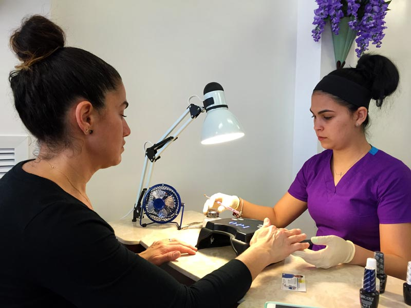 New customer Araceli Rodriguez receives manicure from Diane Silva