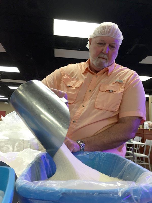 Volunteer Ron Kopplow prepares rice for measuring