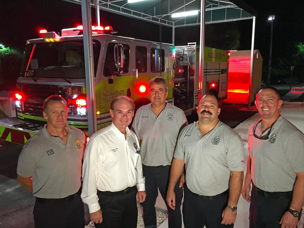 "[L to R] Miami-Dade Fire Rescue Captain Rick Bond, Palmetto Bay Mayor Eugene Flinn and members of ""C"" Platoon Shift man Station 62"