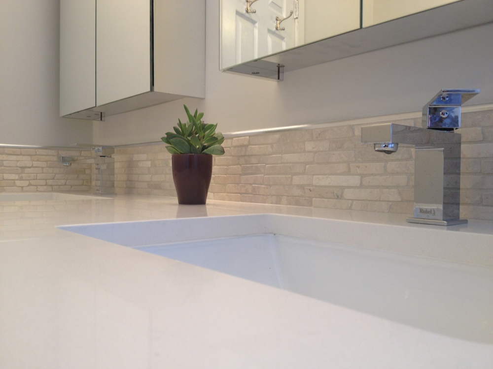 Quartz countertops, stone backsplash and double vanity.
