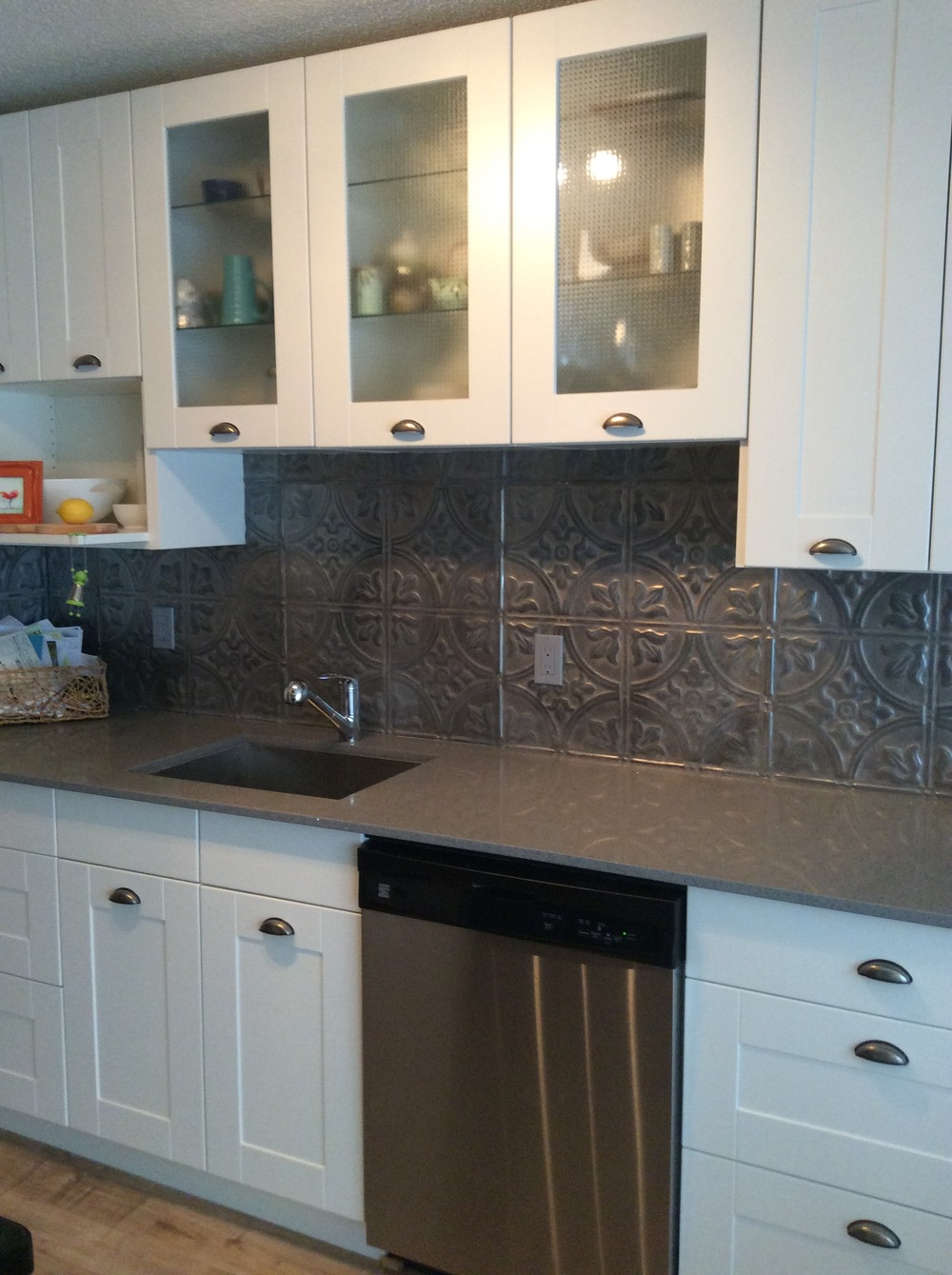 Ikea kitchen, quartz countertops, tin tile backsplash.