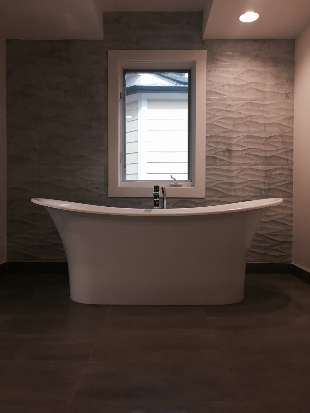 Victoria and Albert volcanic limestone bath, Ziva Leaves tile by Artistic Tile.