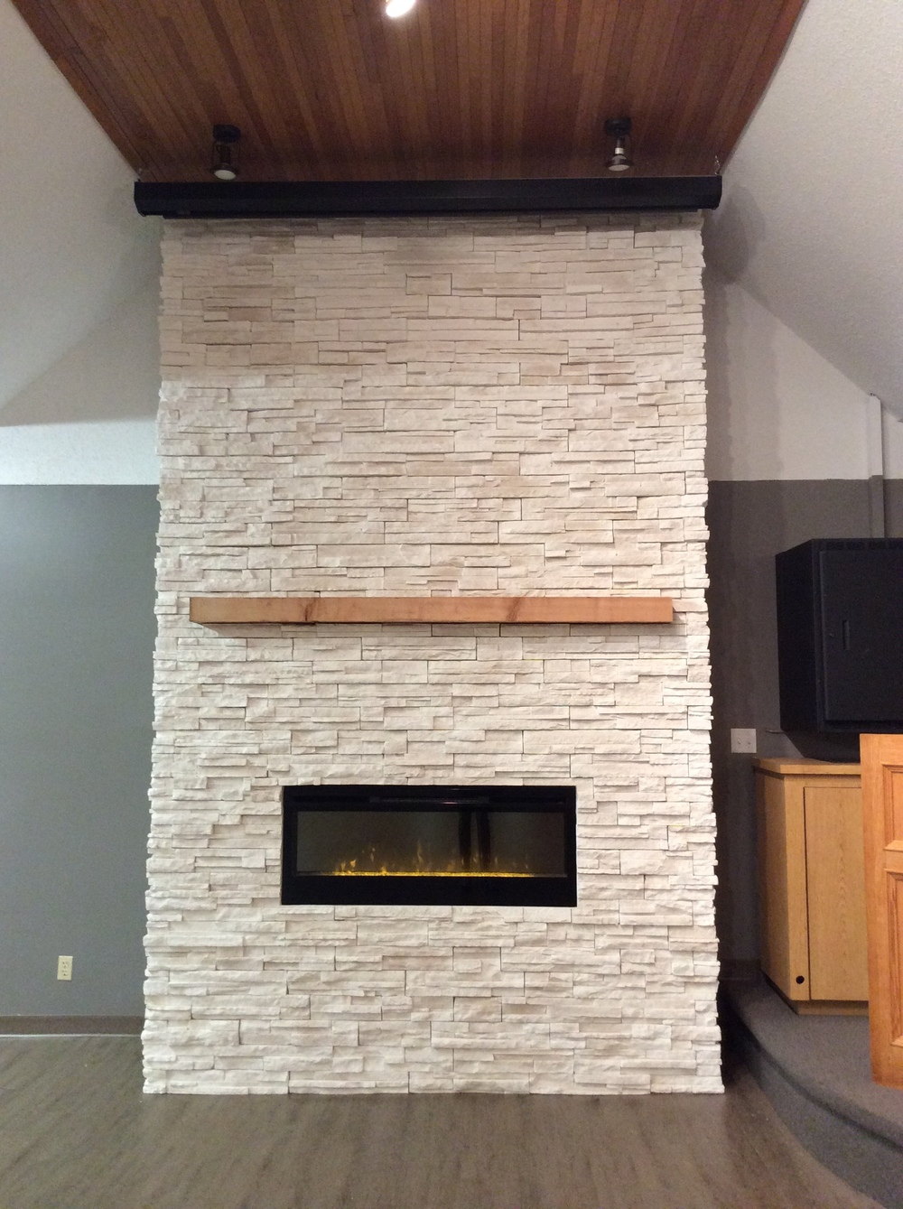 Wood look vinyl flooring, Split faced stone fireplace, rustic mantel.