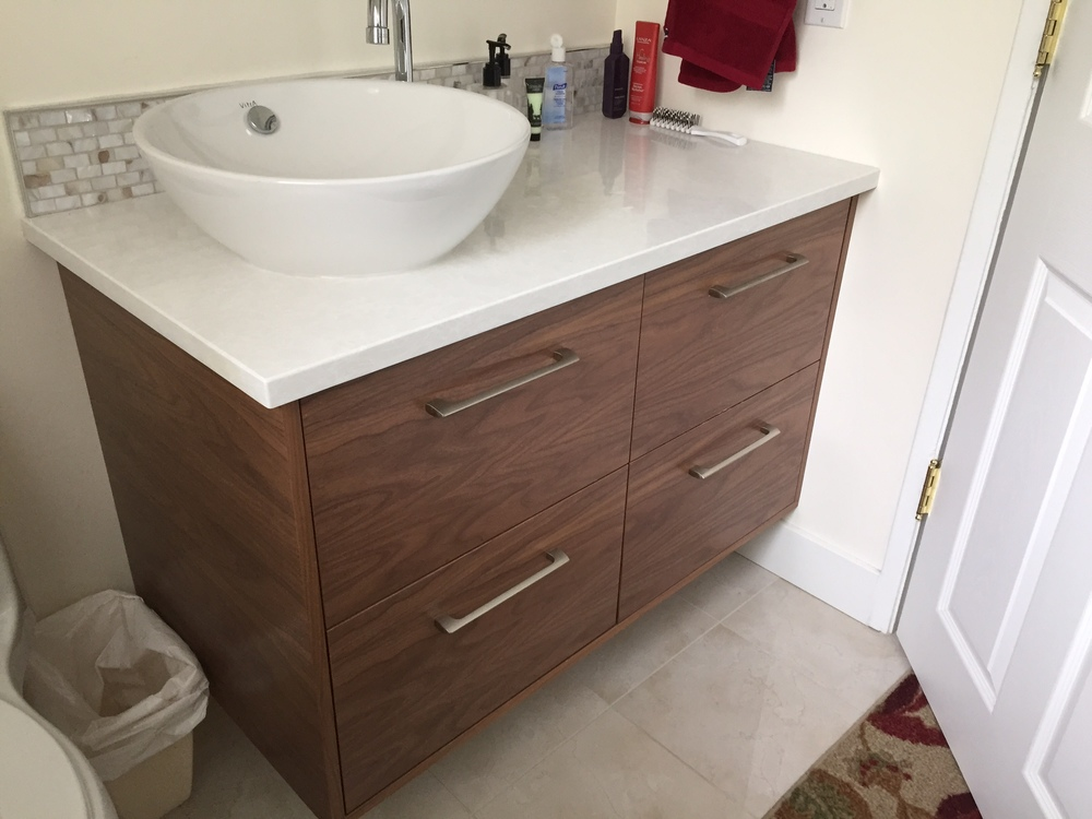 Floating custom walnut vanity cabinet, mother of pearl backsplash.