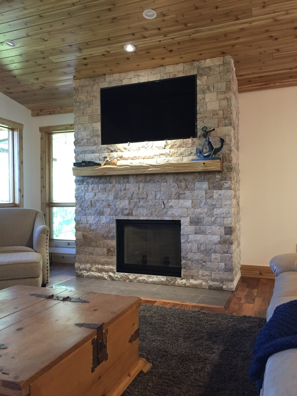 Rustic stone fireplace with live edge birch mantel and porcelain hearth.
