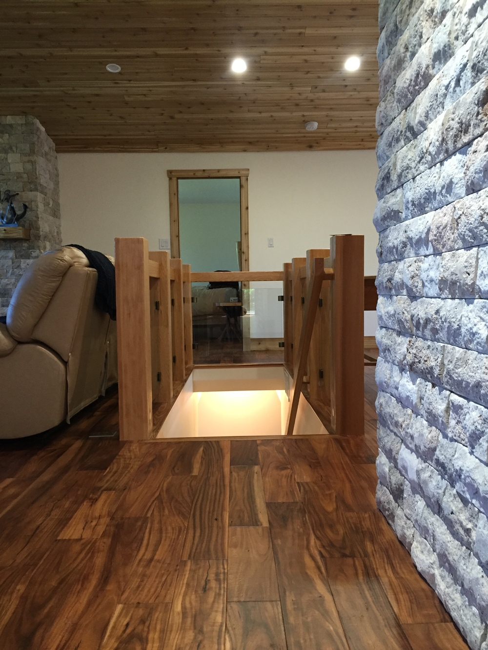 Cedar beam and glass stair surround, acacia hardwood, rustic stone feature wall.