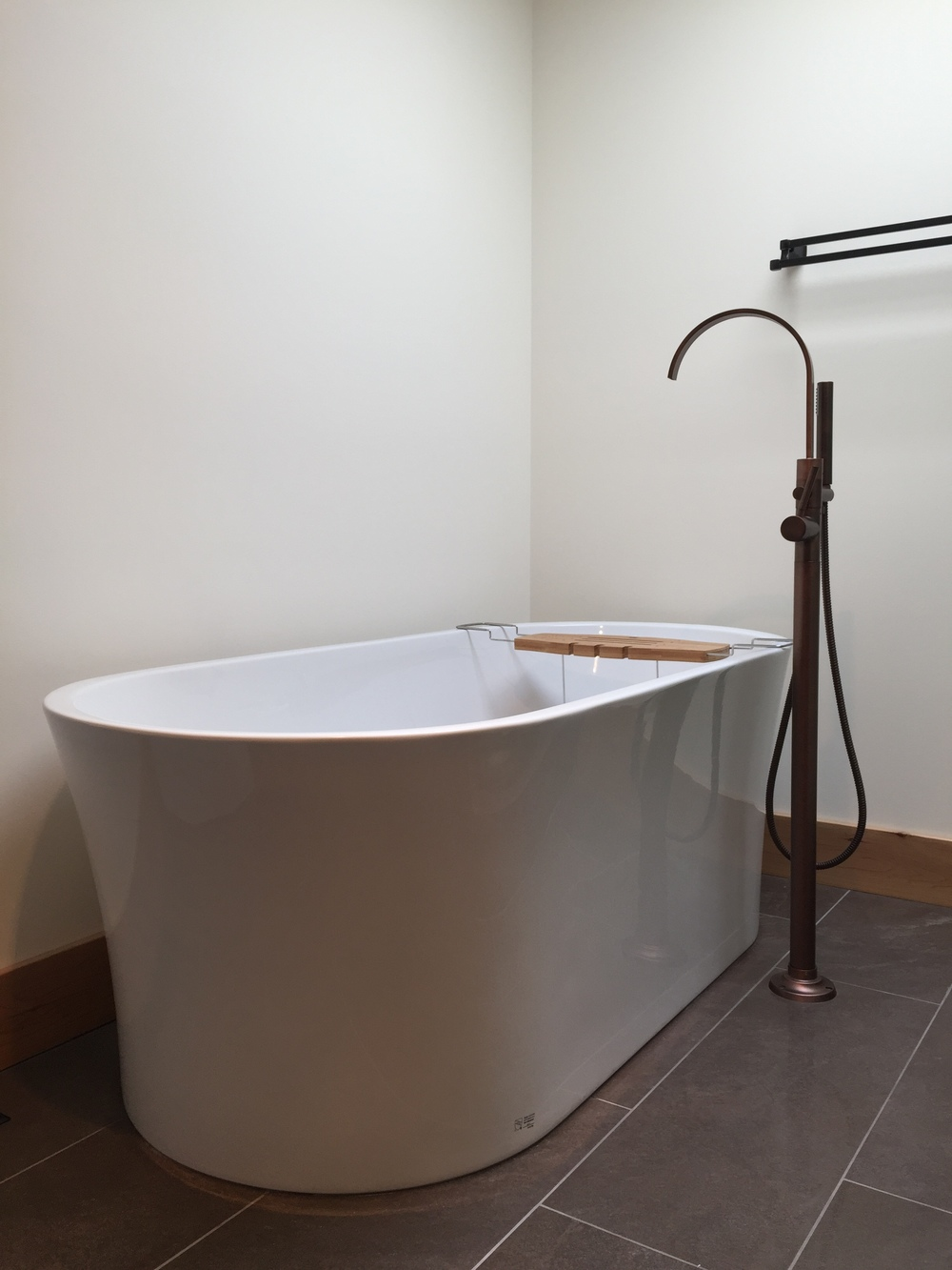 Freestanding acrylic bathtub and antique bronze tub filler, large format polished porcelain tile.
