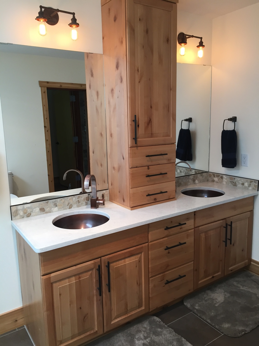 Custom double vanity, vintage inspired light fixtures, white quartz countertop.