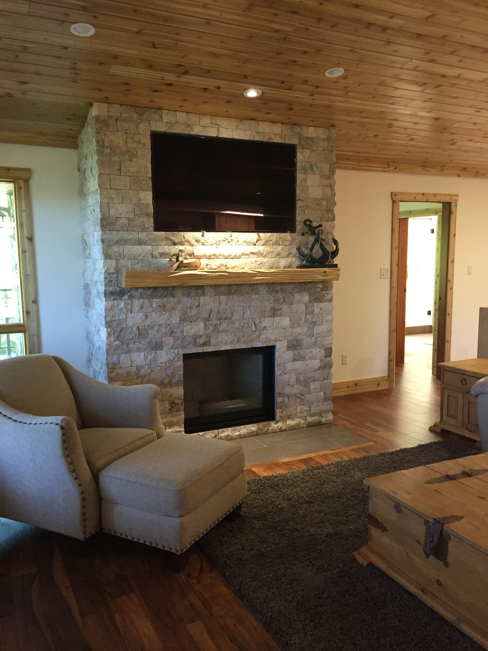 Stone fireplace, live edge birch mantle, inset television, cedar ceiling.
