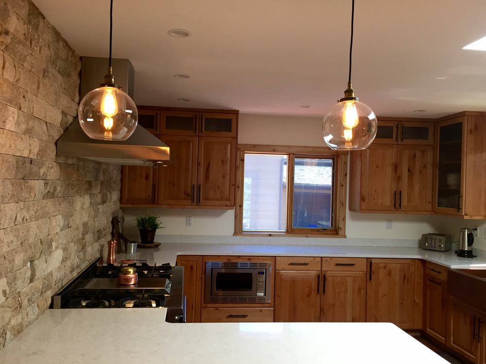 White quartz countertop, vintage inspired industrial pendant lights, professional range and range hood, stone backsplash.