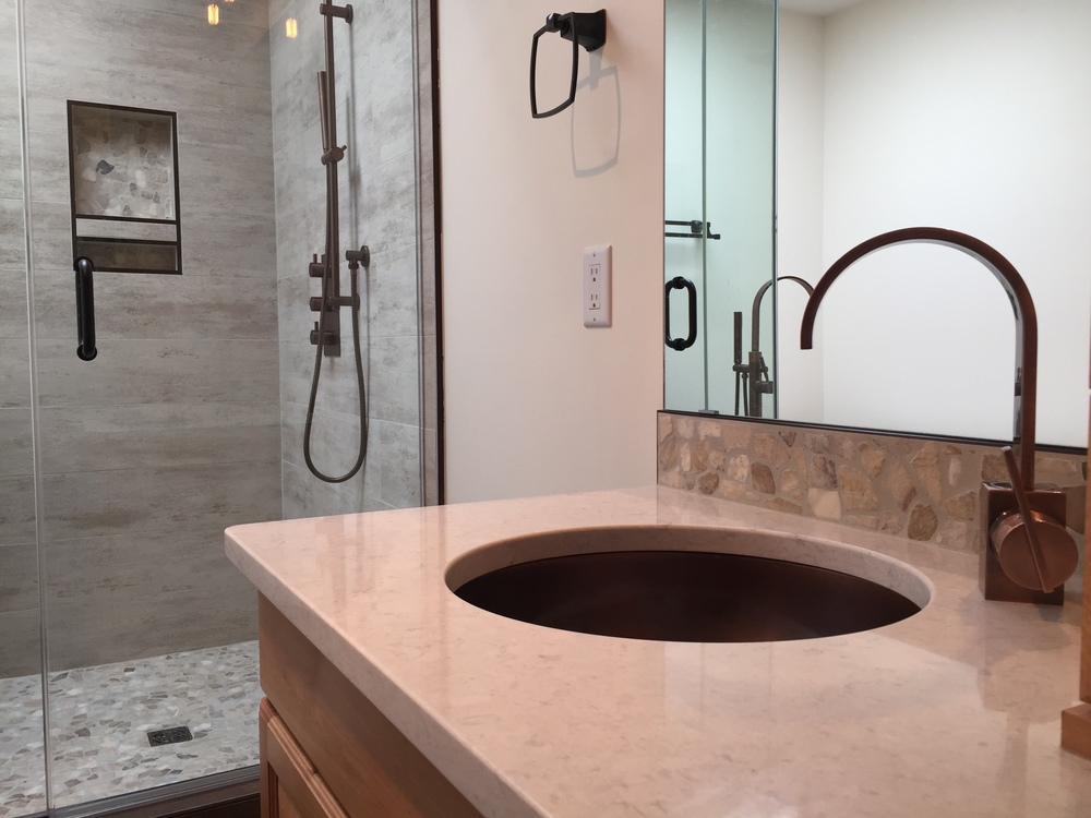 Custom shower, quartz countertops, pebble backsplash, aged bronze faucet.