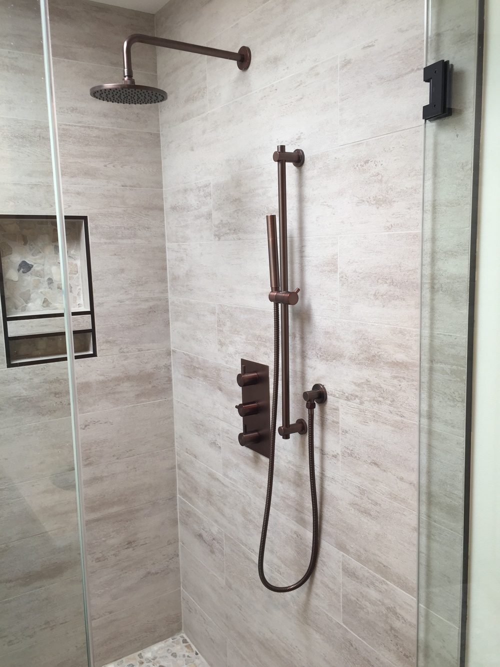 Custom shower, porcelain tile, pebble floor, recessed shower shelves, antique bronze fixtures.