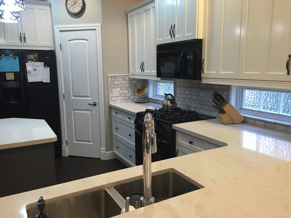 White Quartz countertop, marble backsplash, painted cabinets